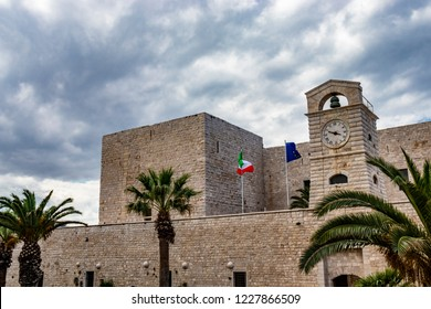 The flags of Italy and of the European community waving on the Swabian castle of Trani. Close-up of the tower with the clock. Stone fortress, on the sea. In Puglia, near Bari, Barletta, Andria.