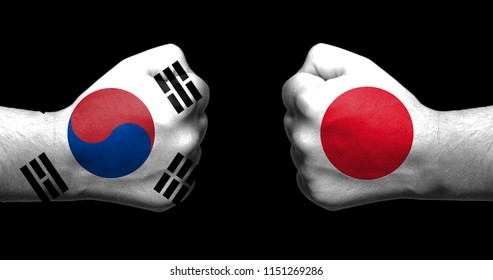 Flags of Japan and South Korea painted on two clenched fists facing each other on black background/Japan–South Korea relations concept