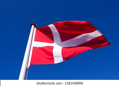 "Flags / Laesoe / Denmark: The Danish national flag ""Dannebrog"" is fluttering in the gusty coastal wind on Laesoe island"