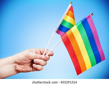 flags of the LGBT community in a hand on a blue background