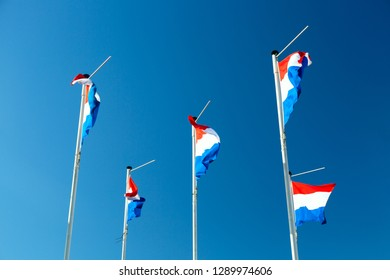 Flags of the Netherlands waving in the wind against blue sky. Holland flags background.
