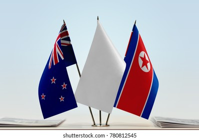 Flags of New Zealand and North Korea with a white flag in the middle