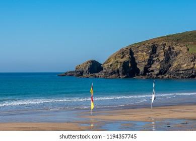 Flags on a Cornish beach with calm sea and clear sky