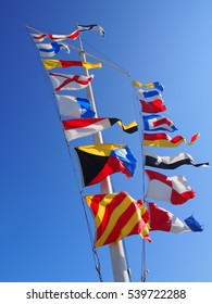 Flags on a flagpole fluttering in the wind on blue sky background