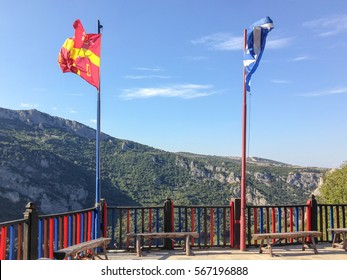 Flags over wooden fence against mountain landscape background. St. John the Baptist hermitage monastery. Imathia, Central Macedonia, Greece.