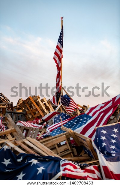 Flags in a pile with the american flag on a flagpole in the center.