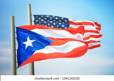 Flags of Puerto Rico and the USA against the background of the blue sky