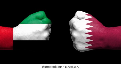Flags of Qatar and Saudi Arabia painted on two clenched fists facing each other on black background/Qatar - Saudi Arabia diplomatic crisis concept