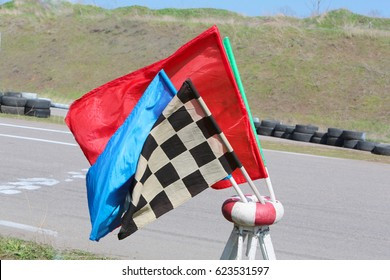 Flags racing. Red, yellow, green, checkered, white black flags on the stand for flags