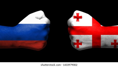 Flags of Russia and Georgia painted on two clenched fists facing each other on black background/Tensed relationship between Russia and Georgia concept