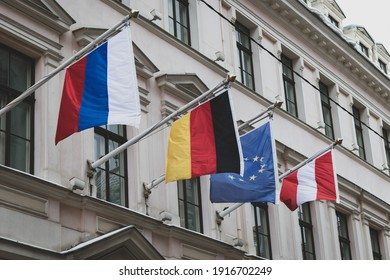 Flags of Russia, Germany, the European Union and Austria on the wall of an old stone building