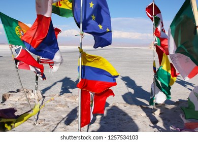Flags in a salt desert of Salar de Uyuni in Bolivia.  Blue Sky and white salt ground. Uyuni, Bolivia