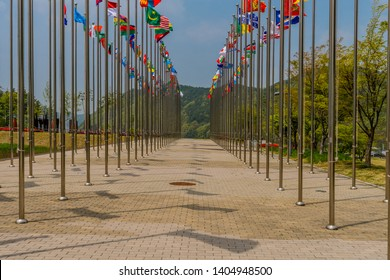 Flags from several nations flying on chrome flagpoles with trees and blue sky in background.