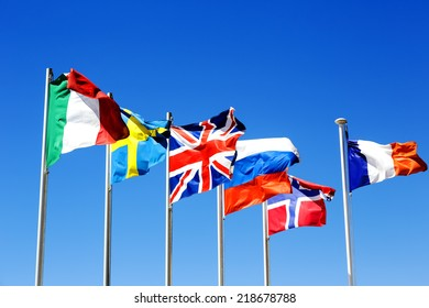 The flags of six countries against a blue sky