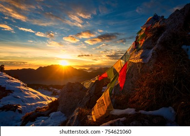 Flags of Tibetan prayers in the mountains with the colors of a warm sunset.