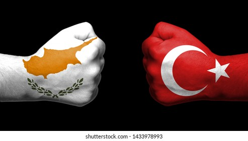 Flags of Turkey and Cyprus painted on two clenched fists facing each other on black background/Tensed relationship between Turkey and Cypruss concept