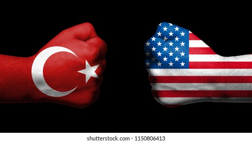 Flags of Turkey and United States painted on two clenched fists facing each other on black background/Turkey - USA relations concept