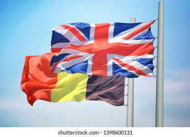 Flags of UK and Belgium against the background of the blue sky