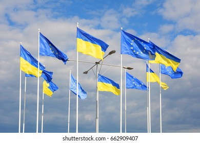 Flags of Ukraine and European Union (EU) against the blue sky.