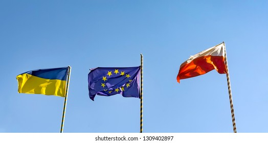 Flags of Ukraine of the European Union and Poland. Three flags on the background of a beautiful blue sky. Panorama
