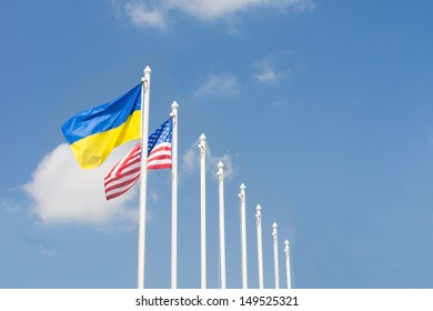 Flags of the Ukraine and United States of America flying in the breeze from a line of metal flagpoles against a clear blue sky with copyspace