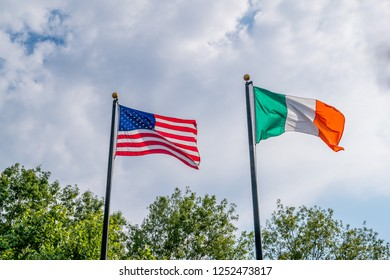 Flags of United states and Ireland fluttering against a blue sky, near Rhode Island irish famine memorial, Providence, USA