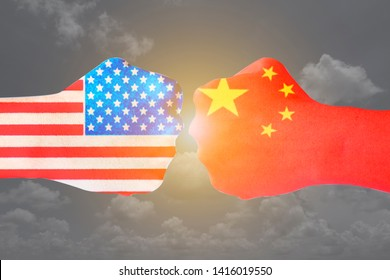 Flags of USA and China  painted on two  fists  on sky background. United States of America versus China trade war disputes concept. - Image