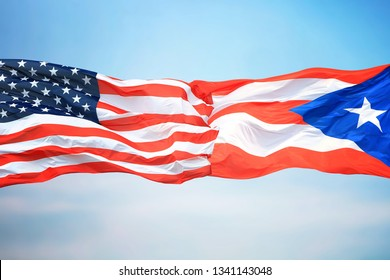 Flags of the USA and Puerto Rico against the background of the blue sky