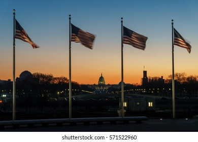 Flags wave in a gentle morning wind as dawn breaks over the United States Capitol and the National Mall in Washington DC