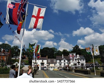 Flags in the wind on the bridge over the River Dee on a sunny and cloudy day. People crossing the bridge on foot with cars and buildings on the other side.  LLangollen, Wales, UK. June 2014.