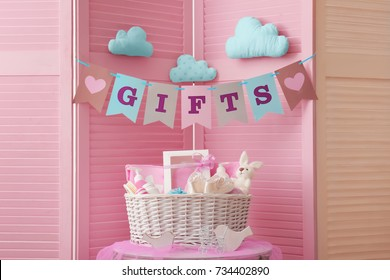 "Flags with word ""gifts"" and basket with baby shower gifts against folding screen"