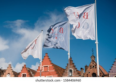 "Flags with the words ""Brugge"" fluttering in the wind against a blue sky. The main square of Bruges in Belgium."
