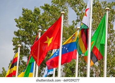 Flags of the world happily blowing in the wind .