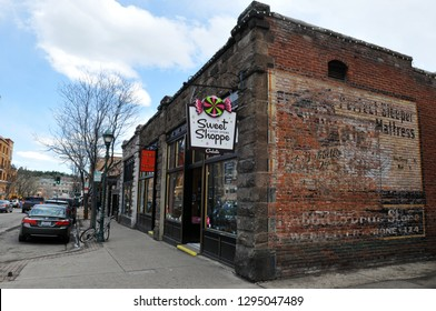 Flagstaff, AZ - March 25, 2017: A faded advertising  is visible on the brick wall of a shop on East Aspen Avenue in downtown Flagstaff, Arizona. The city of 72,000 sits on historic Route 66.