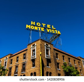 Flagstaff, AZ / USA - 5/14/2017: Hotel Monte Vista as seen from the corner of Aspen Ave looking up.  Perfect blue sky, colorful sign and red brick historic building in contrast.