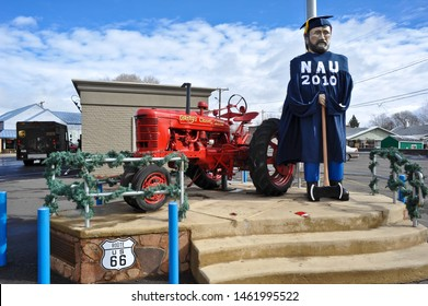 FLAGSTAFF, AZ / USA - DECEMBER 17 2010:  Giant woodsman, in blue cap and gown, holding an axe, with NAU 2010, stands beside a red Tractor for Granny's Closet sports bar and restaurant, on US Route 66.