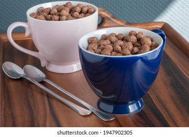 Flakes, chocolate balls in large pink and blue porcelain mugs and long small spoons on a wooden breakfast tray. Dry sweet breakfasts.