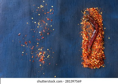 Flakes of red hot chili peppers and one dryed chili pepper over dark blue canvas as background