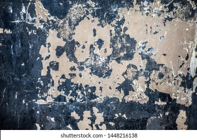 Flaking black painted plaster on a wall.