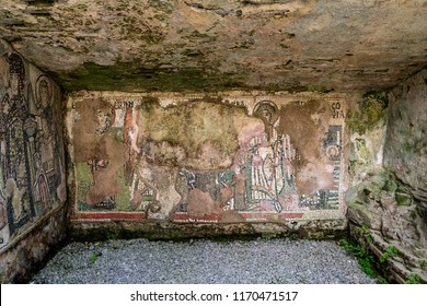 Flaking mosaic figures in a wet ancient roman cave wall.
