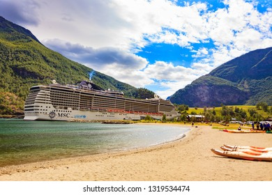 FLAM, NORWAY - JUNE 28, 2018: Njord kayak on shore and cruise ship MSC Preziosa on fjord Aurlandsfjord in norwegian tourist destination Flam village.