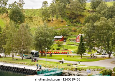 Flam, Norway-August 16, 2014 -  People and touristic buses at Flam village port.