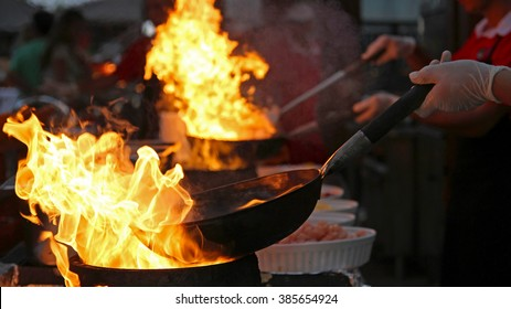 Flambe Chef Cooking in Outdoor Kitchen. Professional chef in a commercial kitchen cooking flambe style. Chef Flambe Cooking.