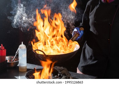 Flambe frying pan wok, cooking on fire. Pan-Asian cuisine. Street food
