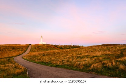 Flamborough, Yorkshire, UK. Dawn breaks over the landscape and the modern lighthouse on a fine autumn morning, at Flamborough, Yorkshire, UK.