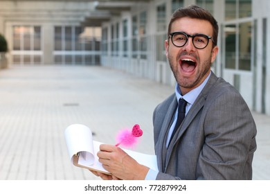 Flamboyant businessman taking notes with a cute pink pen