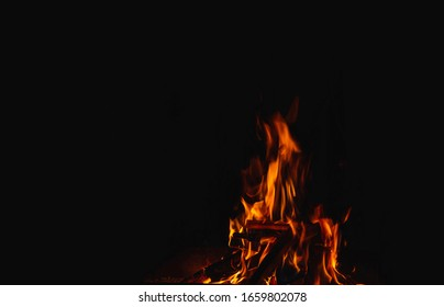 flame, burning wood giving heat and light on a black background, close-up