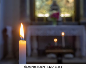 The flame of a candle with the church altar in the background
