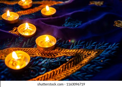 Flame candle lamps for the evening prayers. Diwali lighting on blue sari with golden embroidery