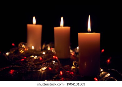 Flame candles with decorative lights on black table background